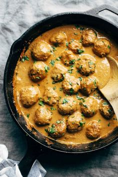 Meatless meatballs in a pan with sauce with wooden spoon.