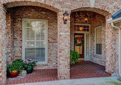 The covered front porch with its decorative brick archways and detailed accents. Brick Archway, Brick And Stone, Front Elevation, Full Bath, Home Values, View Photos, Front Porch, Photo Galleries, New Homes