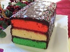 This tri-colored cake is inspired by the classic Italian rainbow cookies, with colorful layers of almond cake sandwiched together with fruit preserves and covered with a chocolate ganache icing. Rainbow Cookie Cake, Italian Rainbow Cookies, Rainbow Cakes, Italian Rainbow Cake Recipe, Italian Cookies, Italian Christmas Desserts, Christmas Recipes, Italian Desserts, Christmas Baking