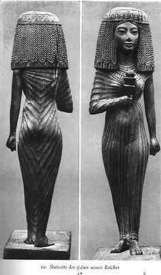 Escultura tallada que nos ilustra la típica reina de Egipto.  Nos muestra el tipo de vestidos que se utilizaban y los accesorios en detalles.  Nos da una vista frontar y por la parte trasera para que tengamos una idea concreta de como lucían las reinas de Egipto en esos tiempos.