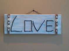 Twig Sign - This is my version of a twig sign I found on Etsy (see Decorating Ideas for the original). I made this using a piece of scrap wood we had sitting around, some twigs from my yard, some twine, a few shells, a couple of flowers, and some craft paint. I had all of the items for this project around my house. The most challenging part was finding twigs to use that would make the letters I needed. It took about a hour to make. I love the finished product. Very cool!