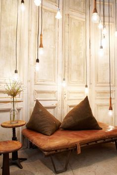 bare bulbs, vintage stools + worn leather all lend a rough, undone vibe to this corner - but the washed wood paneling in this space adds a dose of contrasting elegance