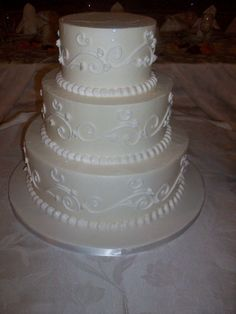 Wedding cake with white detail on cream and fondant board.