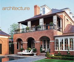 Back of home architecture - second floor porch with potted boxwoods, brick archways on covered porch, sunroom with fantastic windows - Architect Mark Maresca from October 2007 Southern Accents