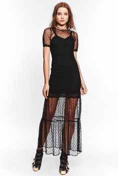 The For Love & Lemons Lil Darlin Maxi Dress in Black Dot features a sheer overlay with scattered woven dots throughout. This piece is complete with an invisible side zipper, button sleeve closure and a separate slip.