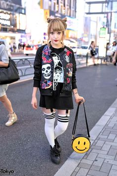 Japanese fashion blogger Coco on the street in Harajuku wearing a punk logos jacket from Kobinai with striped socks, spiked Unif sneakers, and a Bubbles Harajuku smiley face bag.