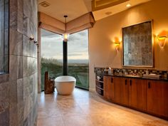 This idyllic master bathroom is truly a desert oasis with a freestanding tub, spectacular views of the outdoors and a muted Southwestern color scheme.