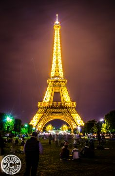 Eiffel tower at night with a bottle of BYOB bottle of wine, just another budget tip for Paris! 7 Tips for Traveling Paris on a Budget