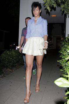 Rihanna in a blue blouse and flirty white skirt