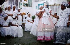 A worshipper is hugged dressed as the goddess Iansa after falling into a trance during a Candomble ceremony on August 17, 2014 in Cachoeira, Brazil. Candomble is an Afro-Brazilian religion whose practitioners often fall into trances during ceremonies and believe they have become possessed by gods, or orixas. The roots of the religion came to Brazil via African slaves while eventually incorporating elements of Catholicism. The state of Bahia received at least 1.2 million slaves from Africa…