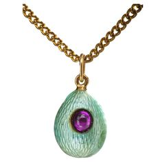 FABERGE Blue-green Enamel Easter Egg Pendant.Overall decorated with sea-green translucent enamel on an engine-turned ground, bezel-set with an oval cabochon ruby measuring 4.2 x 3.6 mm, with a gold suspension ring. circa 1900s