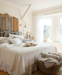 weathered-door-headboard with lovely basket of linens at the foot of the bed.