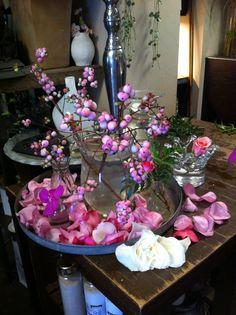 Jeg fikk ansvaret for utstillingen i butikken. Jeg bestemte meg for å dekorere forskjellige steder i butikken etter farger. Her har jeg dekorert med tanke på å bygge ut rosa fargen, med hvite og lyse og mørke rosa roser og bær. Etter hvert kom jeg frem til at vasen der bærene var var for stor så jeg byttet den ut med en flaske med vann. Det samarbeidet bedre med de få bærene jeg hadde.
