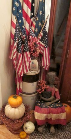 love the idea of a crock filled with different sizes and styles of flags...cute primitive doll