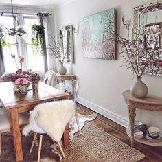 I love this space! Layering rugs, plants hanging in the window, wood, white, fur
