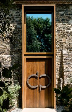 Rusted steel frames project from the traditional stone and plaster walls of this renovated farm house in Spain