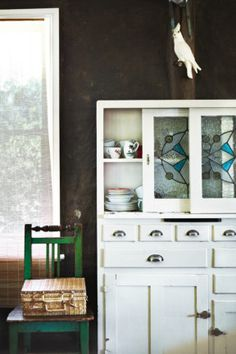 Vintage country house. The Art Deco kitchen cabinet was salvaged from a neighbour's shed and the plaster cockatoo was a housewarming gift.