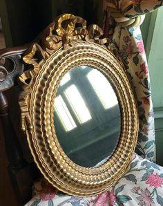 Miroir ovale en bois et stuc doré, le sommet décoré d'un noeud.