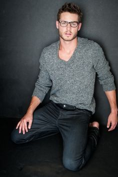 Style. Gray sweater, dark jeans, glasses.