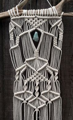 Macramé is one of the most stunning and classic forms of art the 1970s has left with us. This one of a kind wall hanging was inspired by that era of freedom, peacefulness and connecting with the natural world. The rope is soft white 100% cotton and the driftwood was found along rivers in the wild Cascades of Oregon. There is a large chunk of wire wrapped aquamarine colored fluorite that hangs neatly in the center. It is removable and easily hooks and unhooks to the attached brass chain (see…