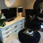 Chic living room with white vintage media cabinet, TV, white Cameroon Juju Hat, white leather Moroccan pouf, came walls paint color, round blue velvet tufted ottoman, black chair, metallic pillow and white shag rug.