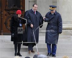 New Michigan Supreme Court Justice Richard Bernstein is helped down the steps during inauguration ceremonies for incoming officials at the state Capitol in Lansing, Mich., on Thursday, Jan. 1, 2015. Bernstein is legally blind. (AP Photo/The Detroit News, David Coates)