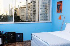 Quarto de hóspedes com decoração moderna e colorida. Os quartos ganharam doses de cor! Os hóspedes podem aproveitar um local azul e tranquilizante e ler na cama graças à luminária de piso laranja, além de apreciarem uma série de quadros apoiados na parede. Eles foram feitos especialmente para o morador pelo artista Thiago Morales e surgiram a partir de uma animação que Nikolas produziu.