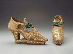 """Pair of women's """"slap-sole"""" shoes      Possibly Italian, about 1670       Italy (possibly)  Dimensions      Overall: 14 x 7.5 x 24 cm (5 1/2 x 2 15/16 x 9 7/16 in.) Other (heel): 7.7cm (3 1/16in.)  Medium or Technique      Leather, silk satin with straw applique, silk laces and tassels, leather lining and sole  Classification      Costumes   Accession Number      44.506a-b"""