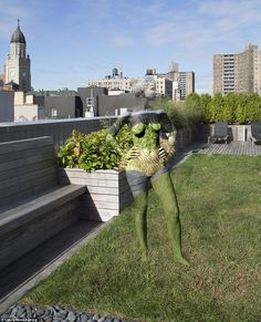 New York artist Trina Merry uses body paint to perfectly camouflage naked models again a backdrop of famous landmarks - like this woman who blends into the rooftop view and skyline of East Village in New York
