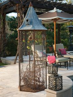 A pair of peach-faced lovebirds live in this large bird cage that sits poolside on this Mediterranean patio. Stone pavers and a vine-covered ramada complete the aesthetic.