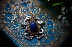 Voici un superbe médaillon que j'ai fait avec une estampe représentant deux serpents qui enlacent une magnifique pierre de Lapis Lazuli (18x13mm).