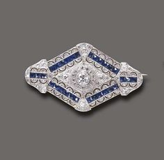 An Art Deco Sapphire and Diamond brooch. Designed as a pierced old European and rose-cut diamond navette-shaped plaque, centering upon an old European-cut diamond within a rose-cut diamond surround, further accented by calibré-cut sapphire trim, mounted in platinum and gold, circa 1920