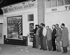 "Men lined-up in front of See's Barber Shop in Tujunga, California, for a haircut, 1930. Overhead sign reads, ""SEE moves to Lower Skid Row."" Little Landers Historical Society. San Fernando Valley History Digital Library."