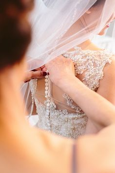 If your dress has buttons running along the length of the back, then add some extra time to your getting-ready schedule to capture this elegant detail.