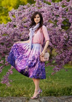 Modest feminine outfit with pink sweater, purple scarf, pink and purple floral midi skirt, and printed fabric heels