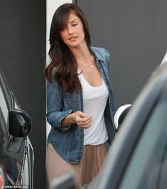 Chic: Minka looked casually elegant in a long skir, white vest top and denim shirt as she left the salon