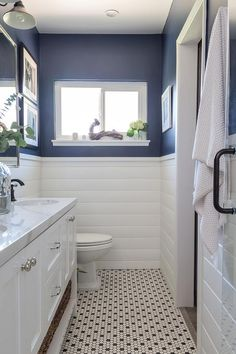 White shiplap bathroom walls accented with a blue upper wall and complement black and white hex floor tiles positioned beneath a white dual bath vanity.