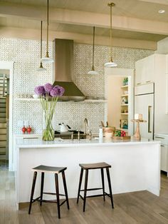 Bright kitchen in Charleston, SC with contemporary white cabinetry - Entire wall tiled - Brass and brushed stainless - Structures Building Company