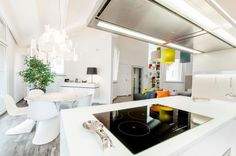 Penthouse : Beautiful Penthouse Design In Pisa, Italy with Bright Interior Designed By Lorenzo Mannini - Sleek Interior Design of Open Floor Penthouse Living Area Designed By Lorenzo Mannini showing Kitchen and White Dining Set and Colorful Living Room Furnitures and Green Indoor Plants Ornaments medium version