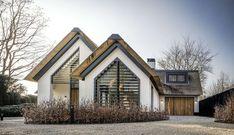 witte villa met rieten dak. Donkere dakkapel. Louvre/facade/shutter