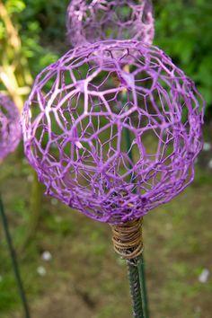 Alliumbollar av hönsnät. Forma bollar av hönsnät kring en boll för att få dem runda, lirka sedan ut bollen och fäst hönsnätet mot ett armeringsstål med ståltråd/najtråd. Doppa i lackfärg.