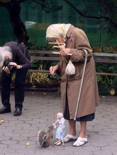 Old woman feeds squirrels using her marionette