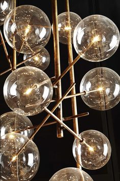 Bolle / Hanging lamp with halogen point light (120 Watt). Transparent blown glass balls. Metal parts in hand burnished brass. The hand burnished brass finish looks naturally spotted and irregular. Due to this craftmade processing, each product is unique and exclusive. *Available in customized versions.