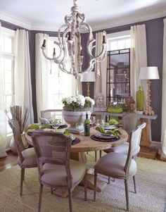 Beautifully designed dining room in lavender, ivory and green. The look of faded grandeur is emphasised by the distressed chandelier and pale colours but the overall appearance is buoyant with interesting artefacts, old and new, on-table foliage and wonderfully large windows.