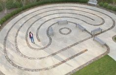 A very formal labyrinth with nice wall paving., lots of seating and a wide path. Perfection would be a tree in the circle at the center/end. Labyrinth Garden, Labyrinth Maze, Labyrinth Meaning, Spiritual Garden, Peace Pole, Prayer Stations, Rock Sculpture, Beautiful Symbols, Ancient Symbols