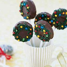 Chocolate-Dipped Oreo Pops     10 lollipop sticks     10 double-stuff Oreo cookies     1 1/2 cup(s) (9 oz) semisweet chocolate chips     1 1/2 tablespoon(s) solid vegetable shortening     Decoration: green sprinkles (jimmies), candy-covered chocolate drops (ice cream topping)