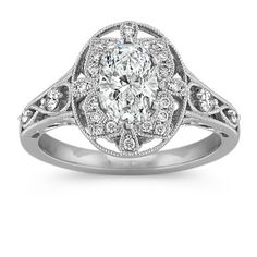 A design worthy of taking note is this halo engagement ring. Twenty-four round diamonds, at approximately .21 carat total weight, are crafted in quality 14 karat white gold adding a glimmer of sparkle throughout the setting. Within the oval halo is a unique, vintage frame design complete with enticing milgrain detail. Your choice of a .75 carat oval diamond would wonderfully complete this gorgeous look.