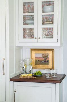 small oil painting decorates the backsplash of the Corner Bar cabinet next to the fridge - Taste Design Inc