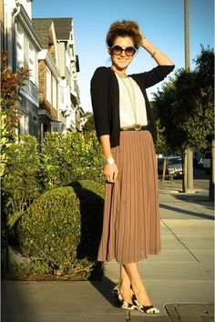 Black cardigan, white top, black belt, rust midi skirt, black and white heels