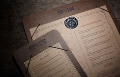 seven - branded particle board menus with elastic/metal brackets to hold.